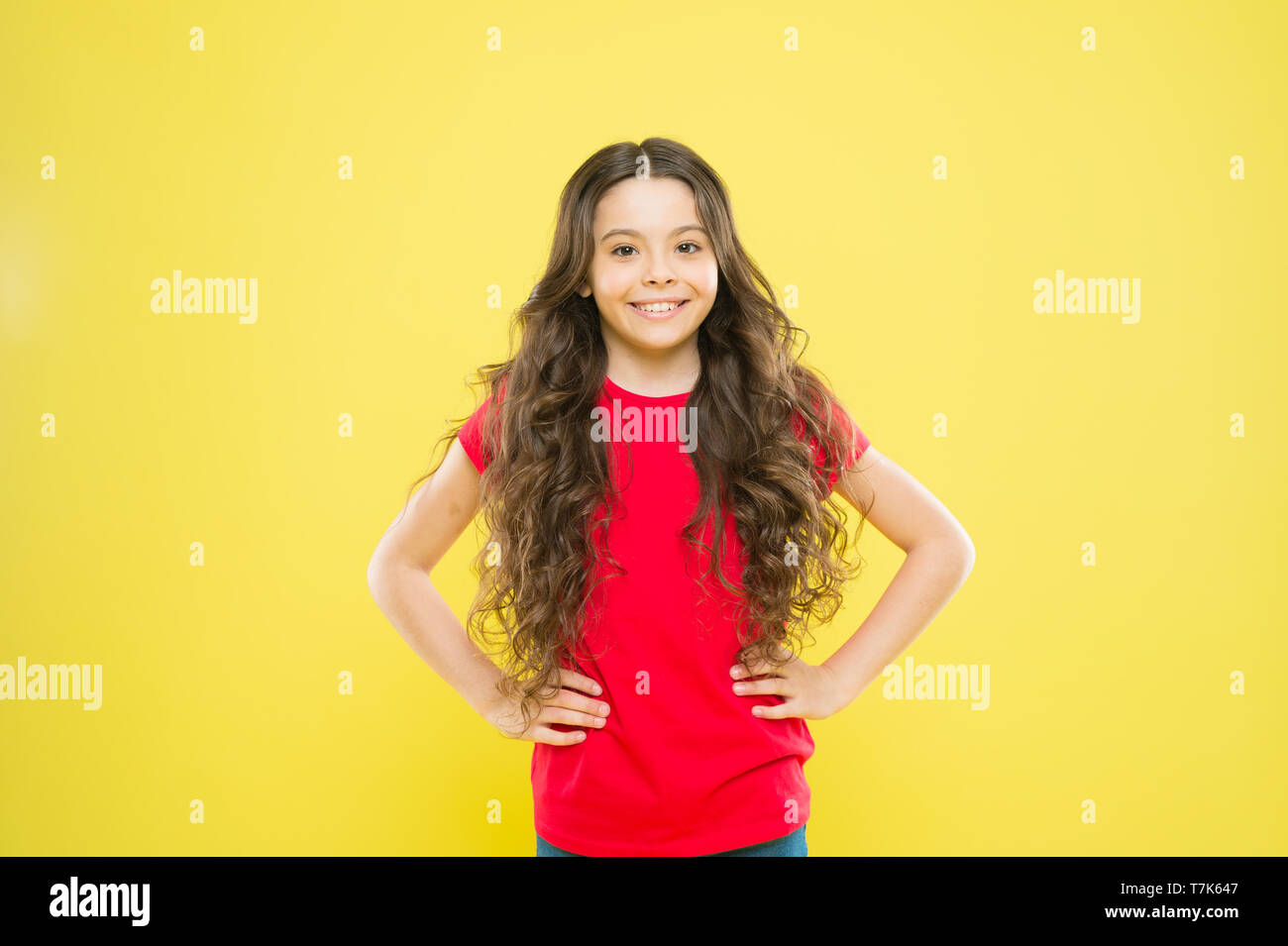 Wind can also damage hair. Girl adorable kid long wavy hair yellow background. Strong persistent winds can create tangles and snags in wavy and curly long hair. Things you doing to damage your hair. - Stock Image