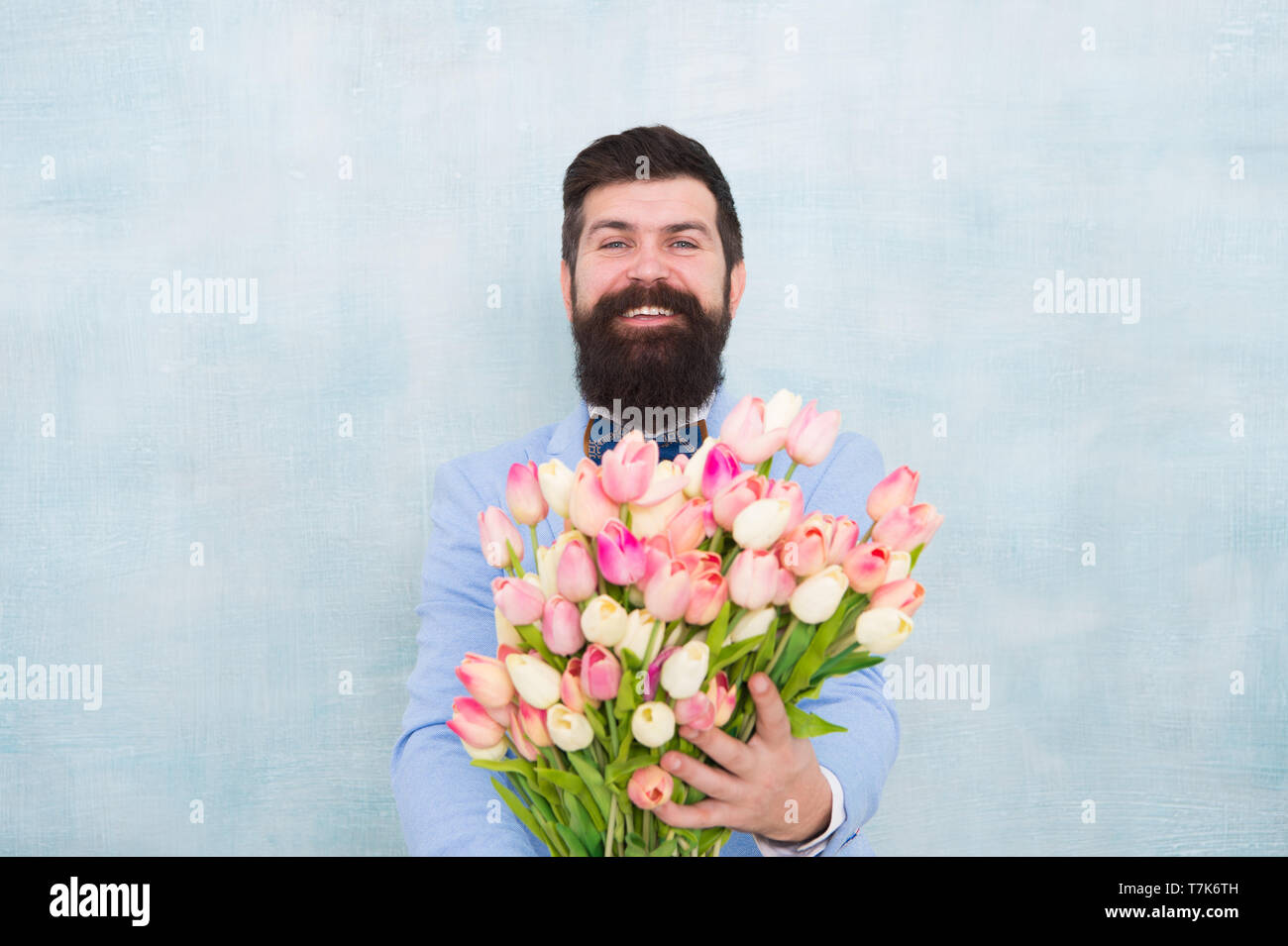 love date with flowers. Happy Birthday. bride groom at wedding party. bearded man in bow tie with tulip flowers. spring bouquet. 8 of march. womens day. Formal mature businessman. Enjoying spring day. - Stock Image