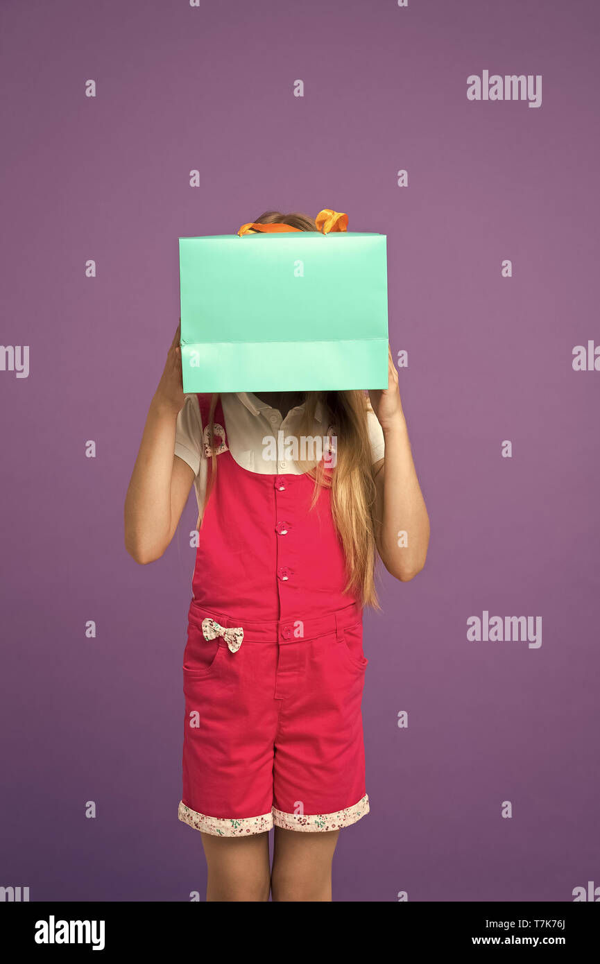 Blind of shopping. Kid holds package in front of face. Simple reminders how to shop smart. Girl cute teenager carries shopping bag. Kid bought clothing summer sale. Seasonal sale concept. - Stock Image