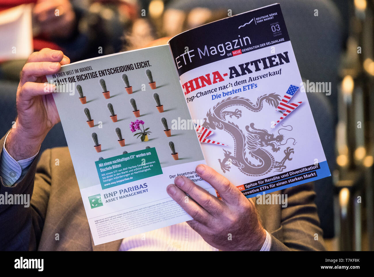 """08 May 2019, Hessen, Frankfurt/Main: At the Annual General Meeting, a shareholder holds the business magazine """"ETF Magazin"""" in his hands. The Annual General Meeting of Deutsche Börse AG is held in the Jahrhunderthalle Frankfurt. Photo: Andreas Arnold/dpa Stock Photo"""