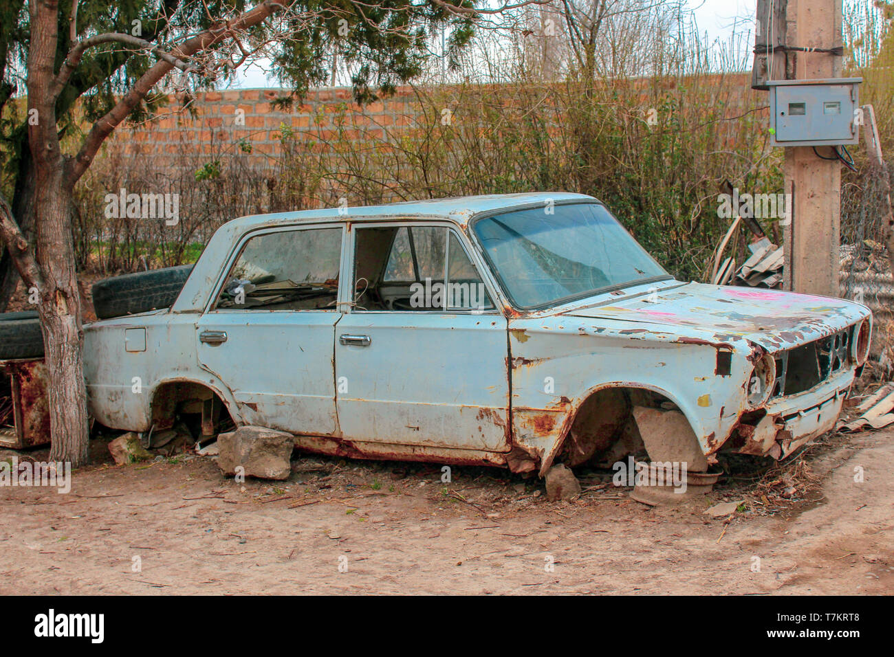 The old, disassembled, rusty and dirty body of the car stands on the outskirts of the city in Armenia. - Stock Image