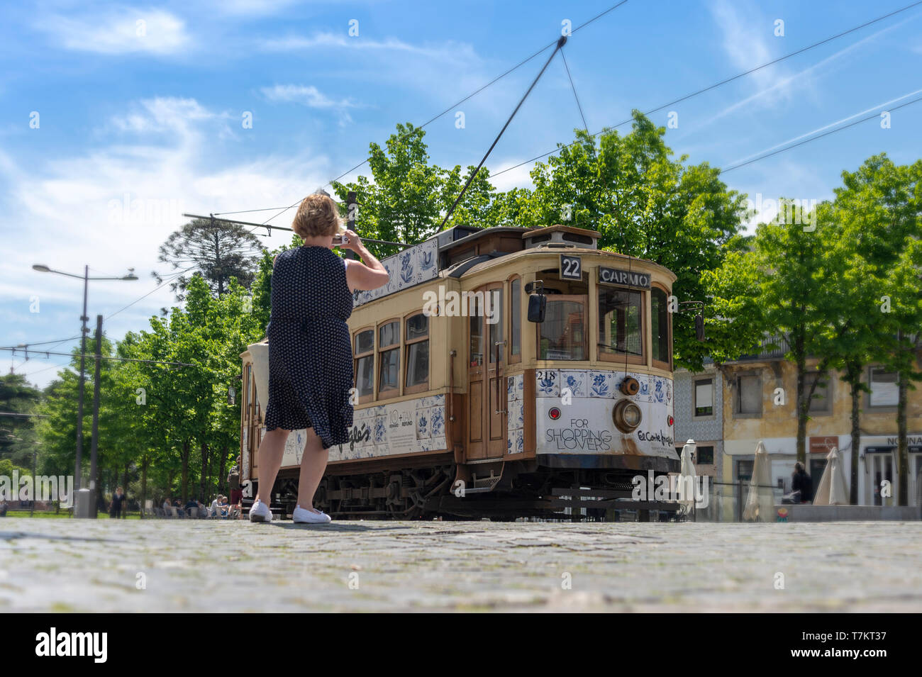 Traditional electric tram in downtown Porto, Portugal with a tourist taking a photograph. Stock Photo