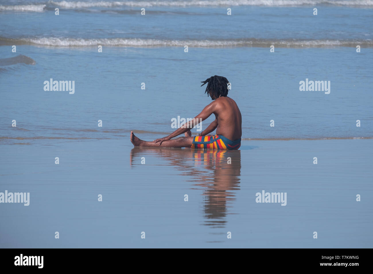 Young boy in colourful striped shorts plays in the waves at Port St Johns, Transkei, South Africa. The sea at Port St Johns is shark infested. - Stock Image