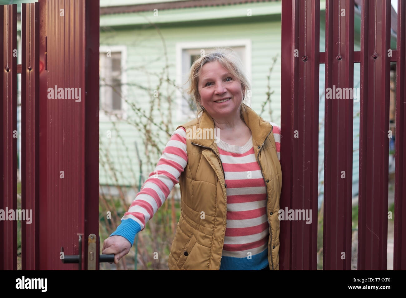 Mature caucasian woman opening the red fence to welcome some guests. - Stock Image