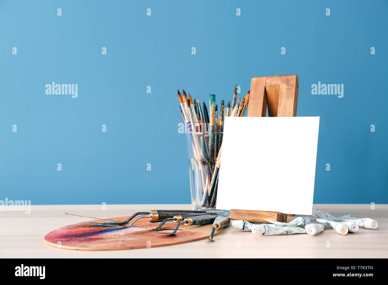 Set of painting tools with canvas on table against color