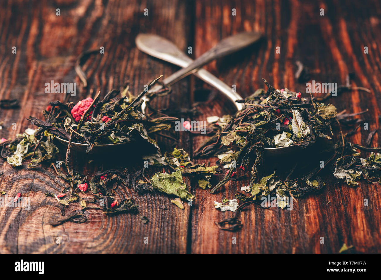 Two spoonfuls of raspberry herbal tea over wooden surface - Stock Image