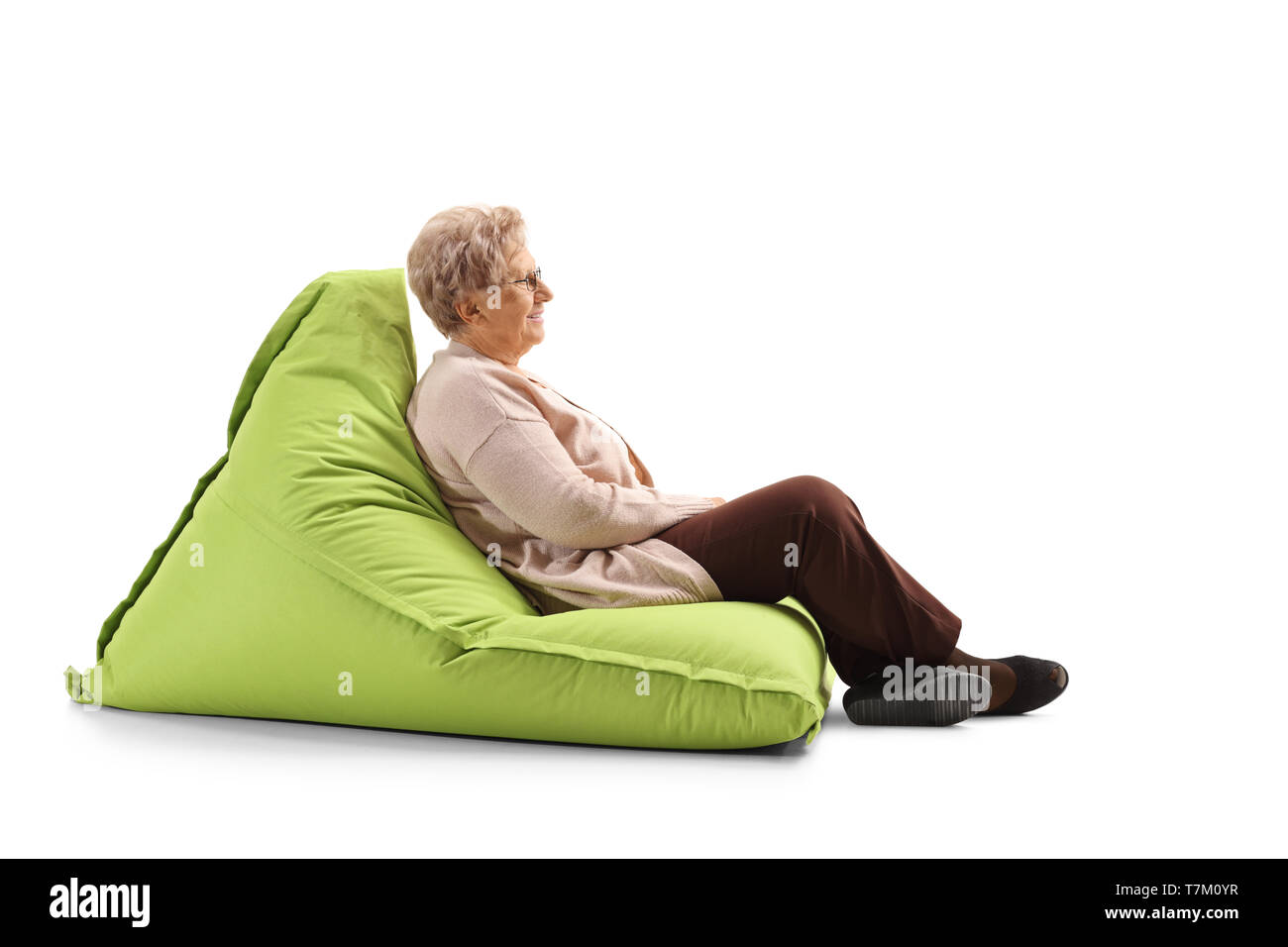 Full length profile shot of a senior woman resting on a bean bag isolated on white background - Stock Image