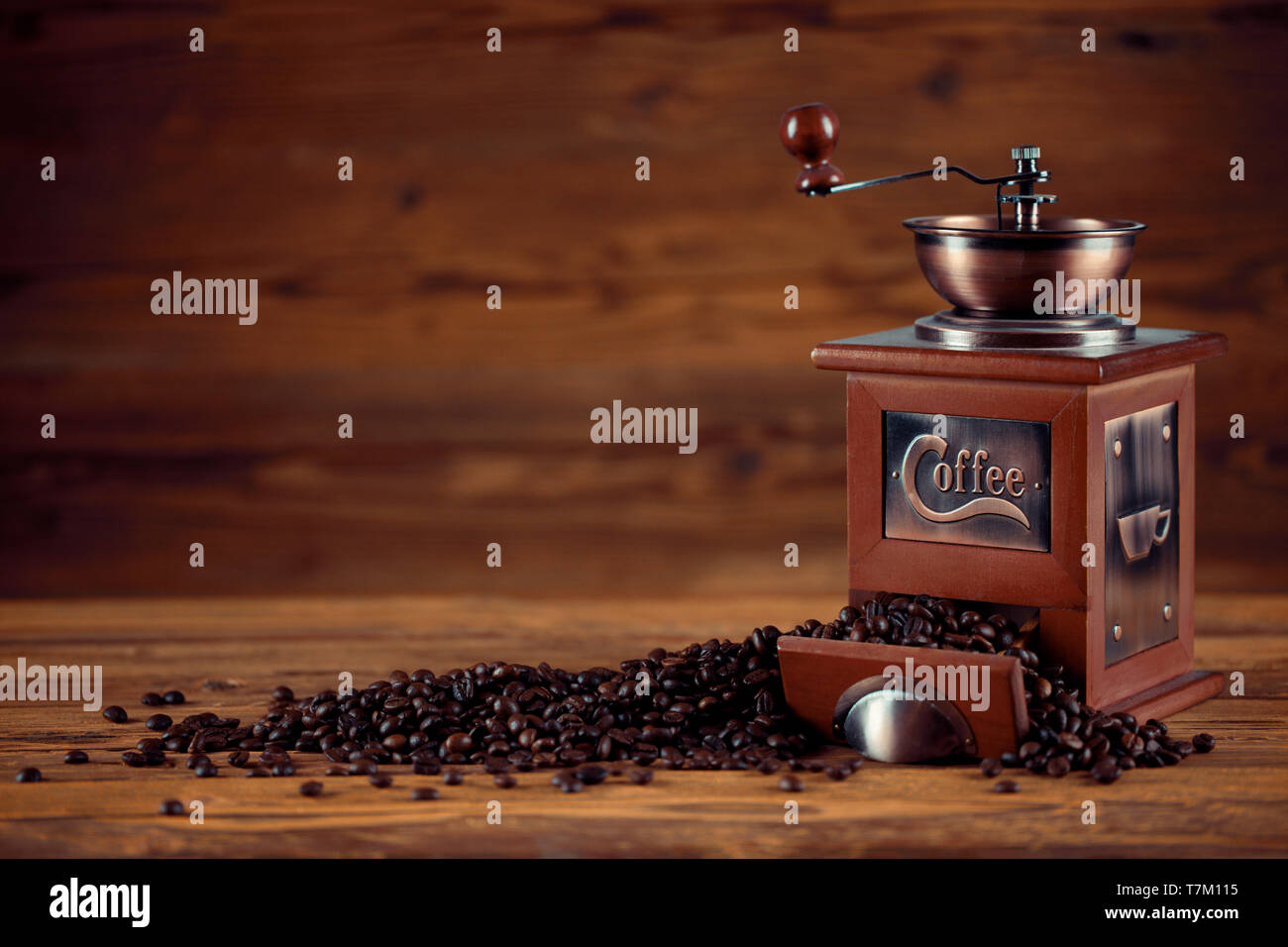 Coffee grinder with coffee beans on wooden background - Stock Image