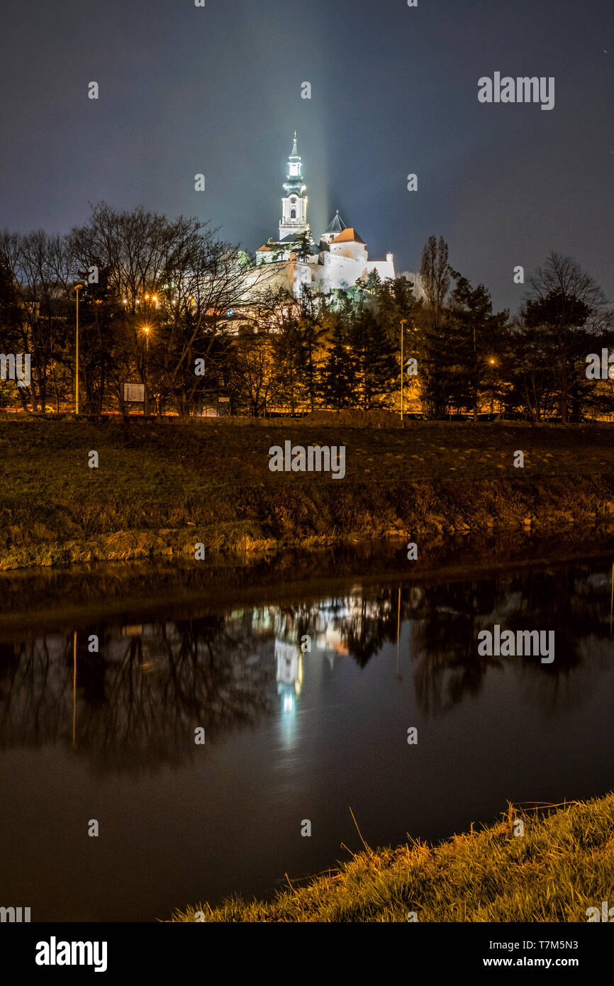 Ancient castle is mirrored in river, Nitra, Slovak republic. Night scene. Cultural heritage. Architectural theme. - Stock Image