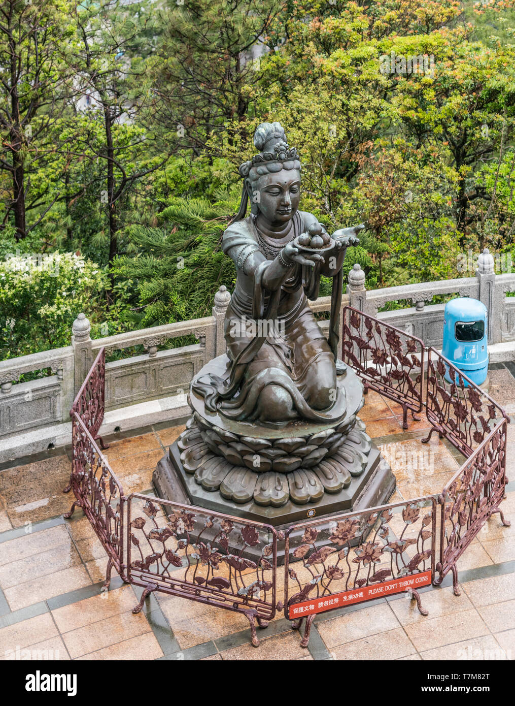 Hong Kong, China - March 7, 2019: Lantau Island. One of the Six Devas offers fruit to Tian Tan Buddha. Bronze statue seen from higher up with green fo - Stock Image