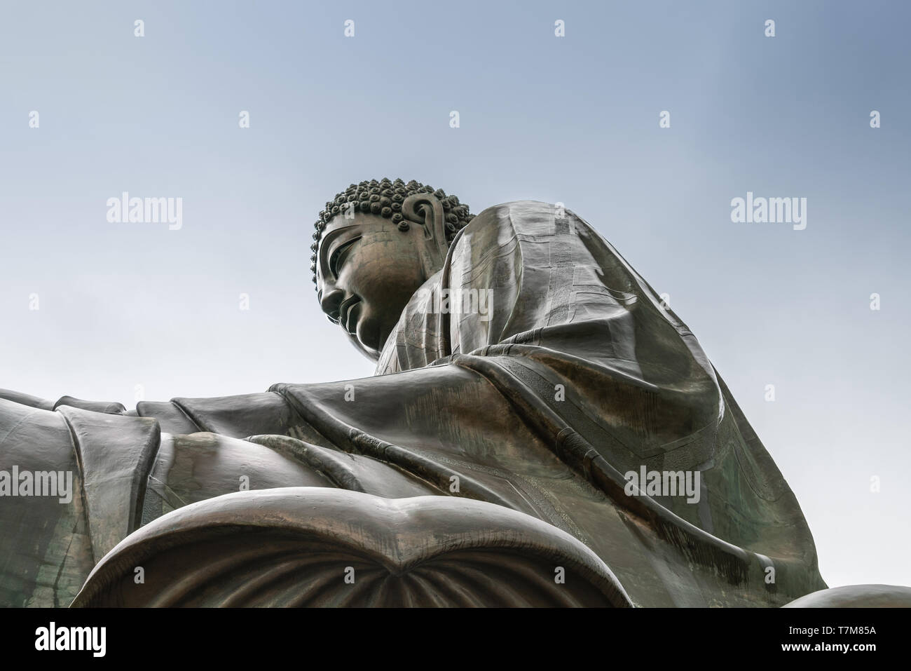 Hong Kong, China - March 7, 2019: Lantau Island. Closeup of Tian Tan Buddha statue from side under showing robe and lotus leaf under light blue sky. - Stock Image