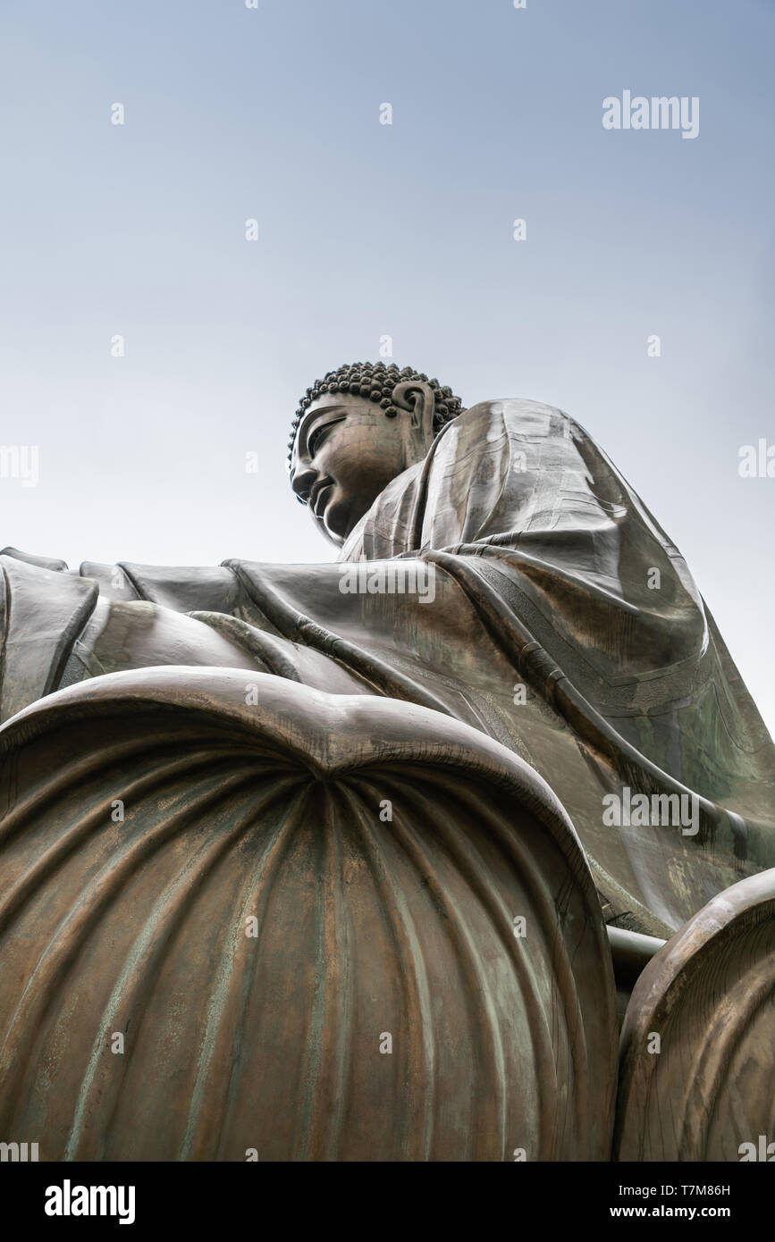 Hong Kong, China - March 7, 2019: Lantau Island. Closeup of Tian Tan Buddha statue from side under showing robe and two lotus leaves under light blue  - Stock Image