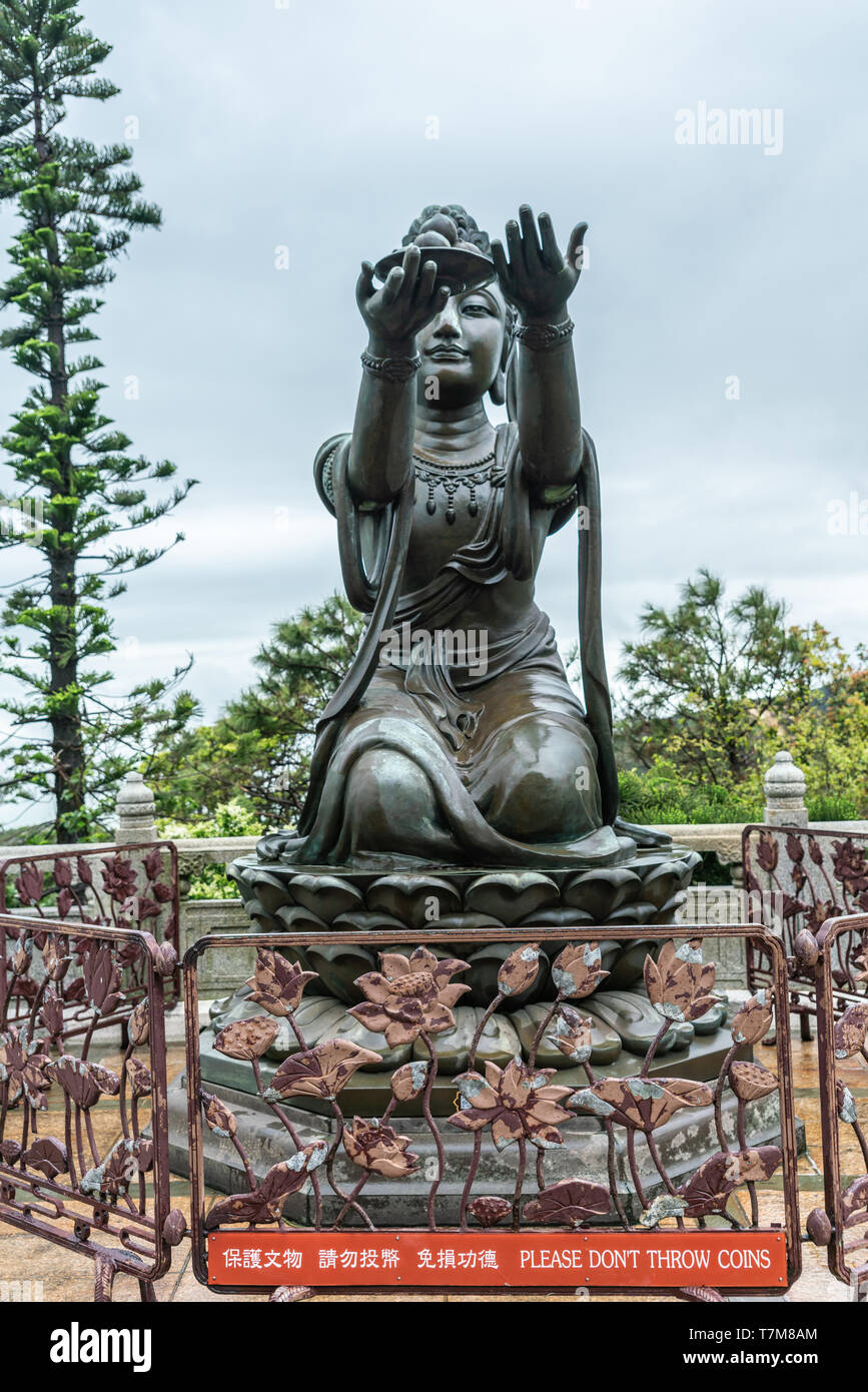 Hong Kong, China - March 7, 2019: Lantau Island. One of the Six Devas offers fruit to Tian Tan Buddha. Bronze statue seen from front with green foliag - Stock Image