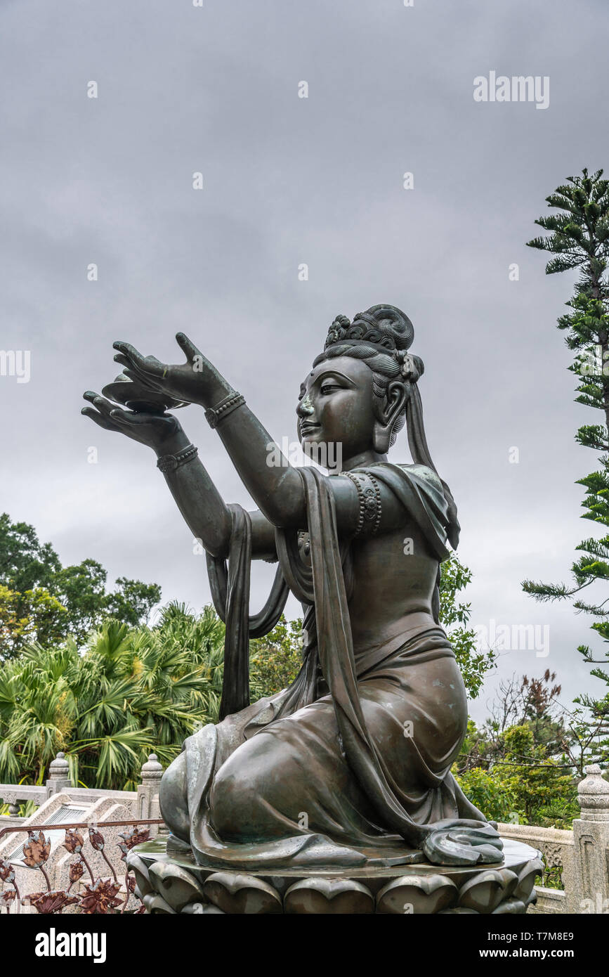 Hong Kong, China - March 7, 2019: Lantau Island. Side Closeup, One of the Six Devas offers fruit to Tian Tan Buddha. Bronze statue seen from front wit - Stock Image