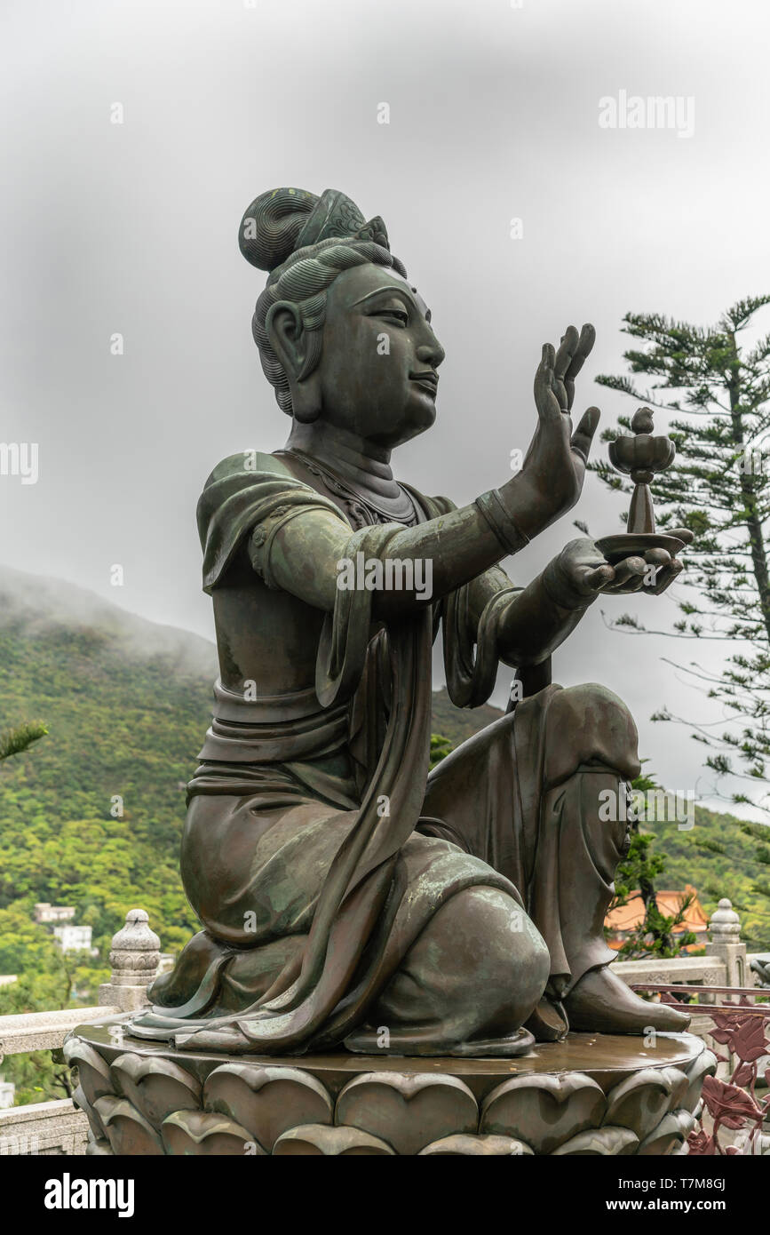 Hong Kong, China - March 7, 2019: Lantau Island. Side Closeup, One of the Six Devas offers lamp to Tian Tan Buddha. Bronze statue seen from front with - Stock Image