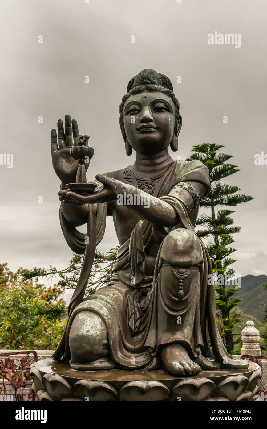 Hong Kong, China - March 7, 2019: Lantau Island. Closeup, One of the Six Devas offers lamp to Tian Tan Buddha. Bronze statue seen from front with gree - Stock Image