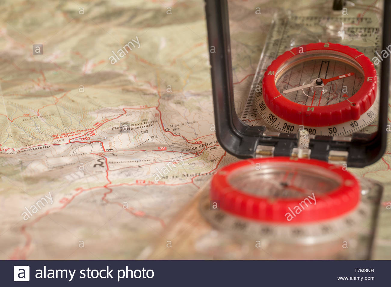 Cartographic compass with mirror used for orienteering, over a topographic map related to an italian area - Stock Image