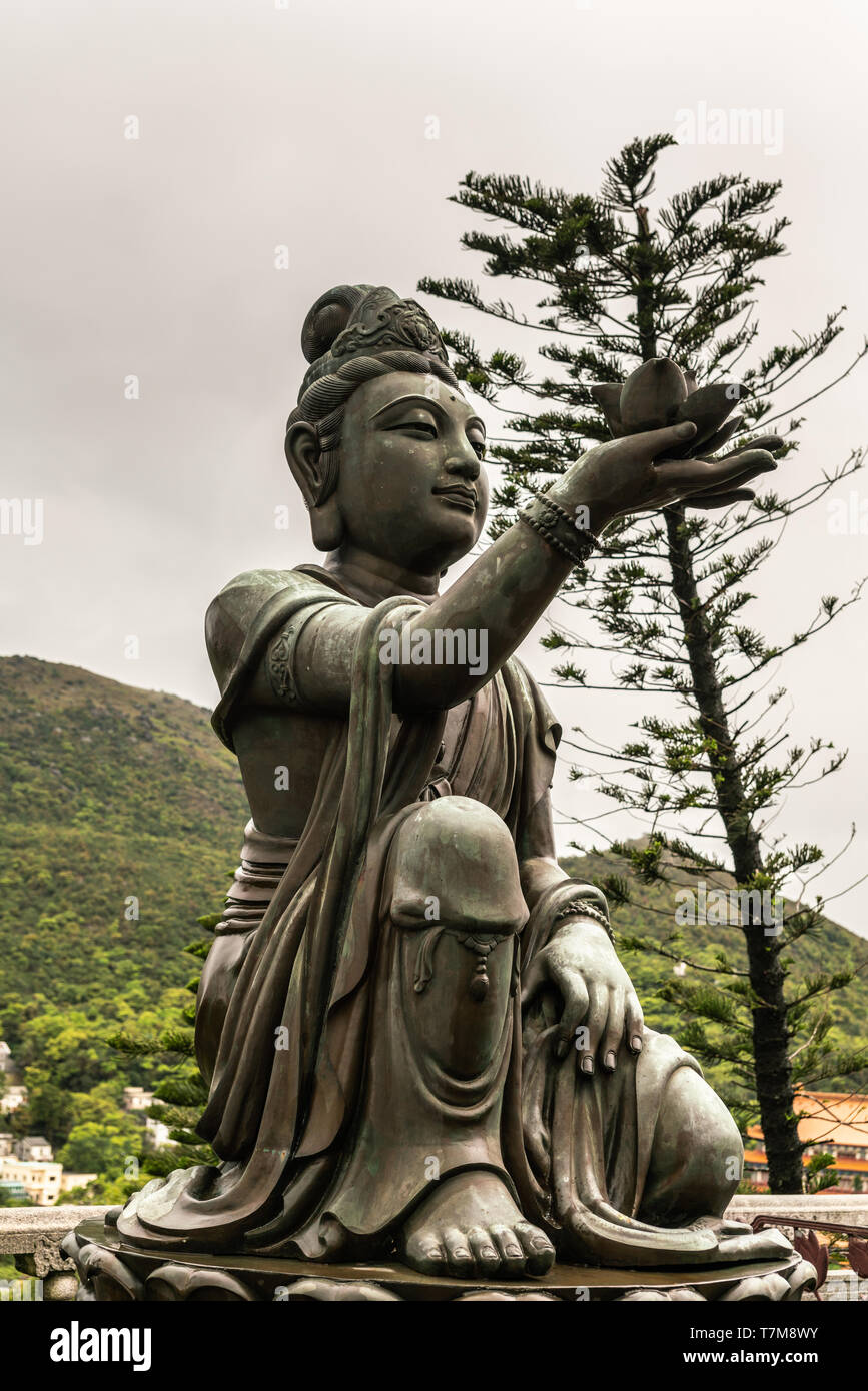 Hong Kong, China - March 7, 2019: Lantau Island. Closeup, One of the Six Devas offers flower to Tian Tan Buddha. Bronze statue seen from front with gr - Stock Image