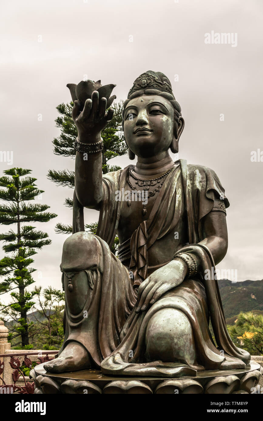Hong Kong, China - March 7, 2019: Lantau Island. Front Closeup, One of the Six Devas offers flower to Tian Tan Buddha. Bronze statue seen from front w - Stock Image