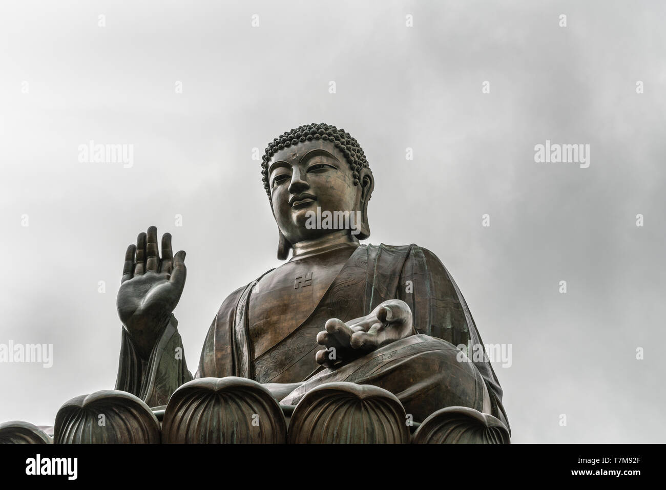 Hong Kong, China - March 7, 2019: Lantau Island. Frontal Closeup of Tian Tan Buddha statue from down under showing face, chest and lotus leaf under si - Stock Image