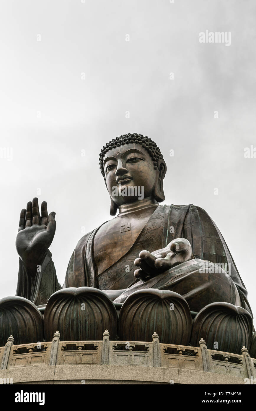 Hong Kong, China - March 7, 2019: Lantau Island. Frontal view of Tian Tan Buddha statue from down under showing face, chest, lotus leaves and stone fe - Stock Image