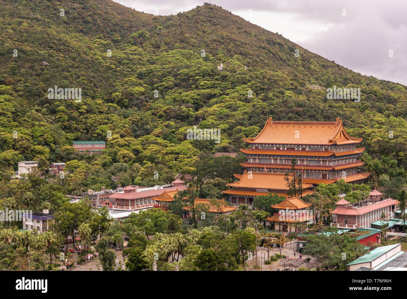 Hong Kong, China - March 7, 2019: Lantau Island. Po Lin Buddhist Monastery seen from platform at Tian Tan Buddha statue. Red roofs between trees and g - Stock Image