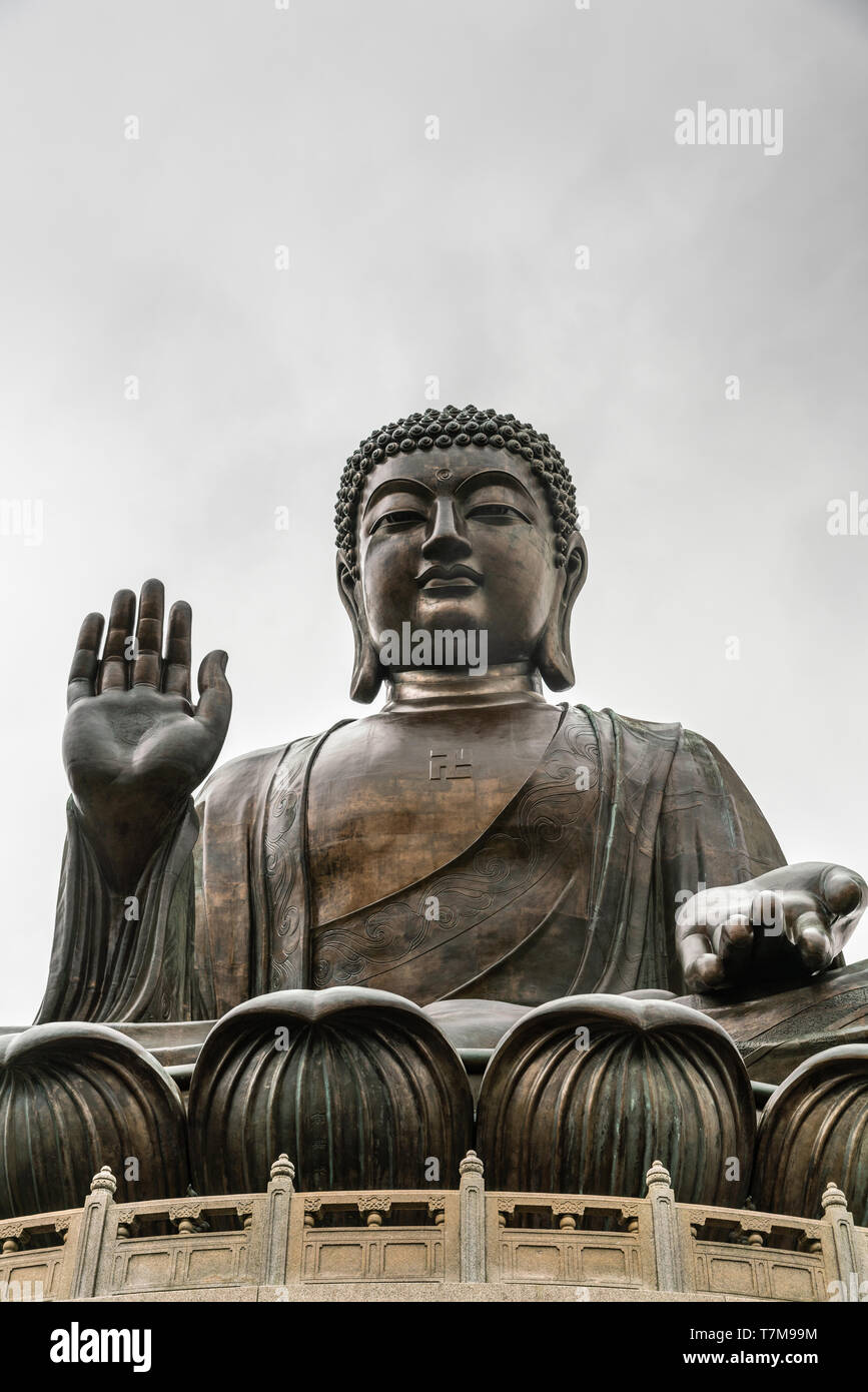 Hong Kong, China - March 7, 2019: Lantau Island. Frontal Facial view of Tian Tan Buddha statue from down under showing face, chest, lotus leaves and s - Stock Image
