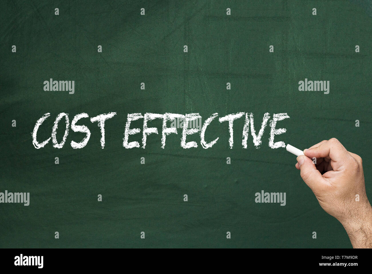 Male's hand writing on blackboard - Cost effective - Stock Image