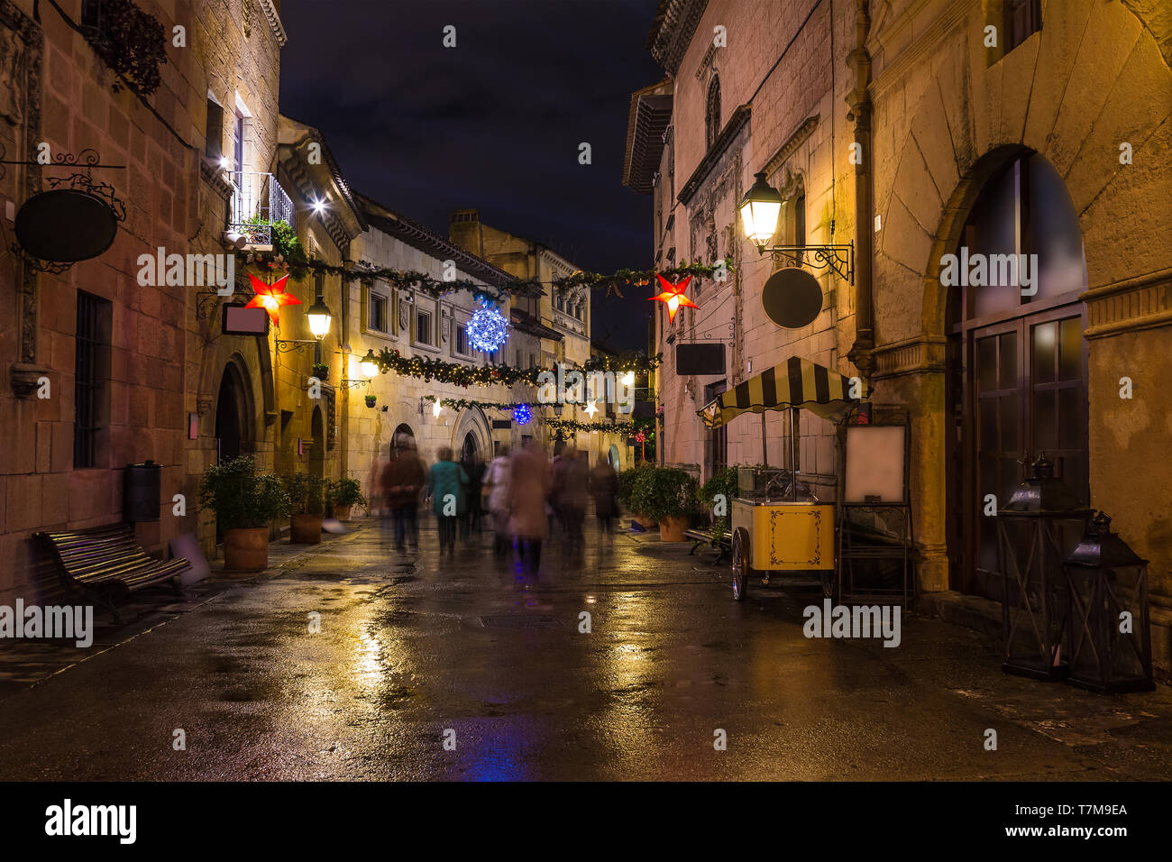 Barcelona, Catalonia, Spain - November 17, 2018: Beautiful night view long-exposure of an illuminated street with motion blurred tourists in the open- Stock Photo