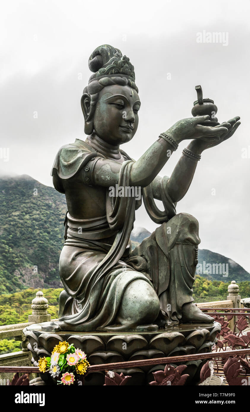 Hong Kong, China - March 7, 2019: Lantau Island. Closeup, One of the Six Devas offers ointment to Tian Tan Buddha. Bronze statue seen from front with  - Stock Image