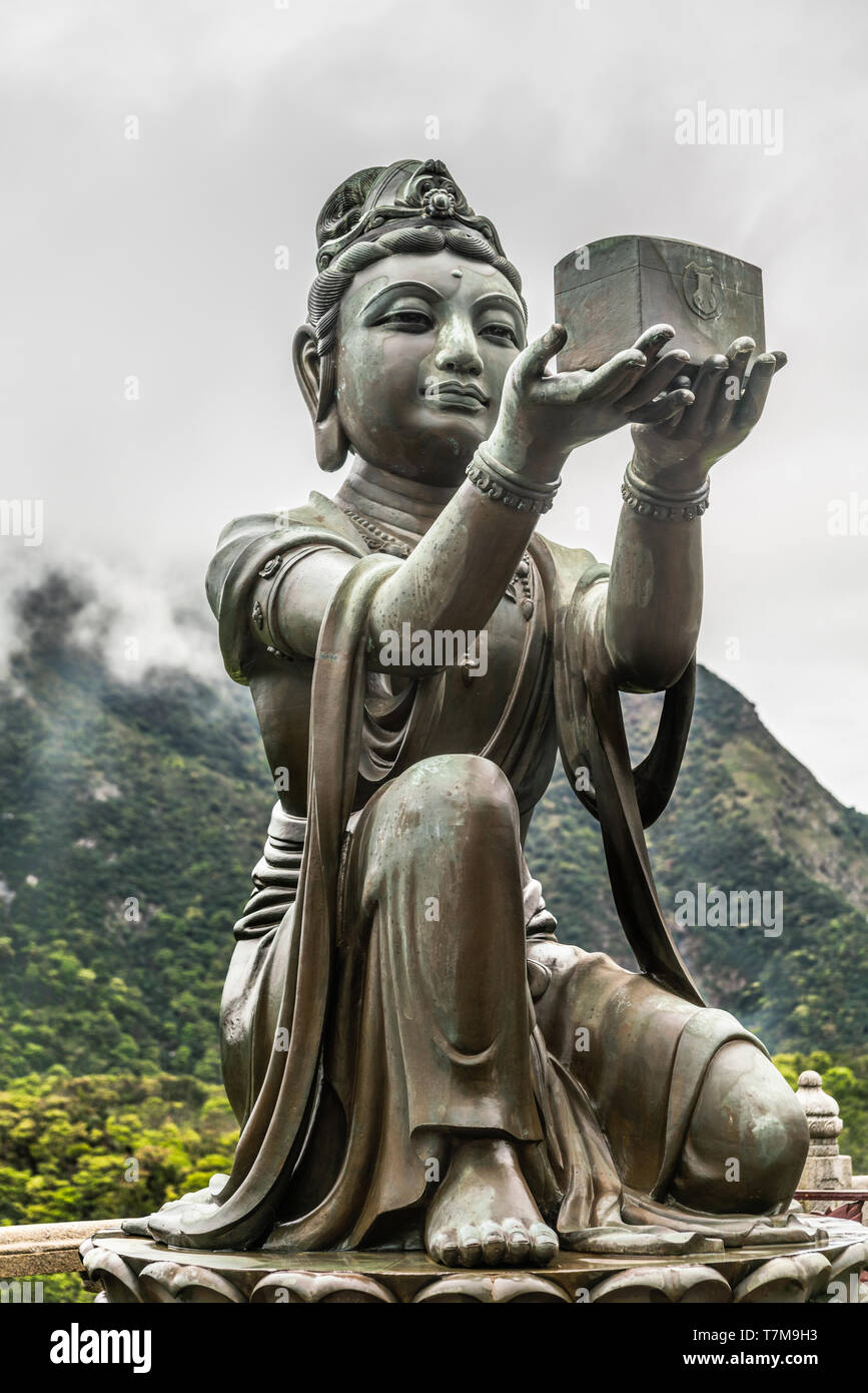 Hong Kong, China - March 7, 2019: Lantau Island. Closeup, One of the Six Devas offers music box to Tian Tan Buddha. Bronze statue seen from front with - Stock Image