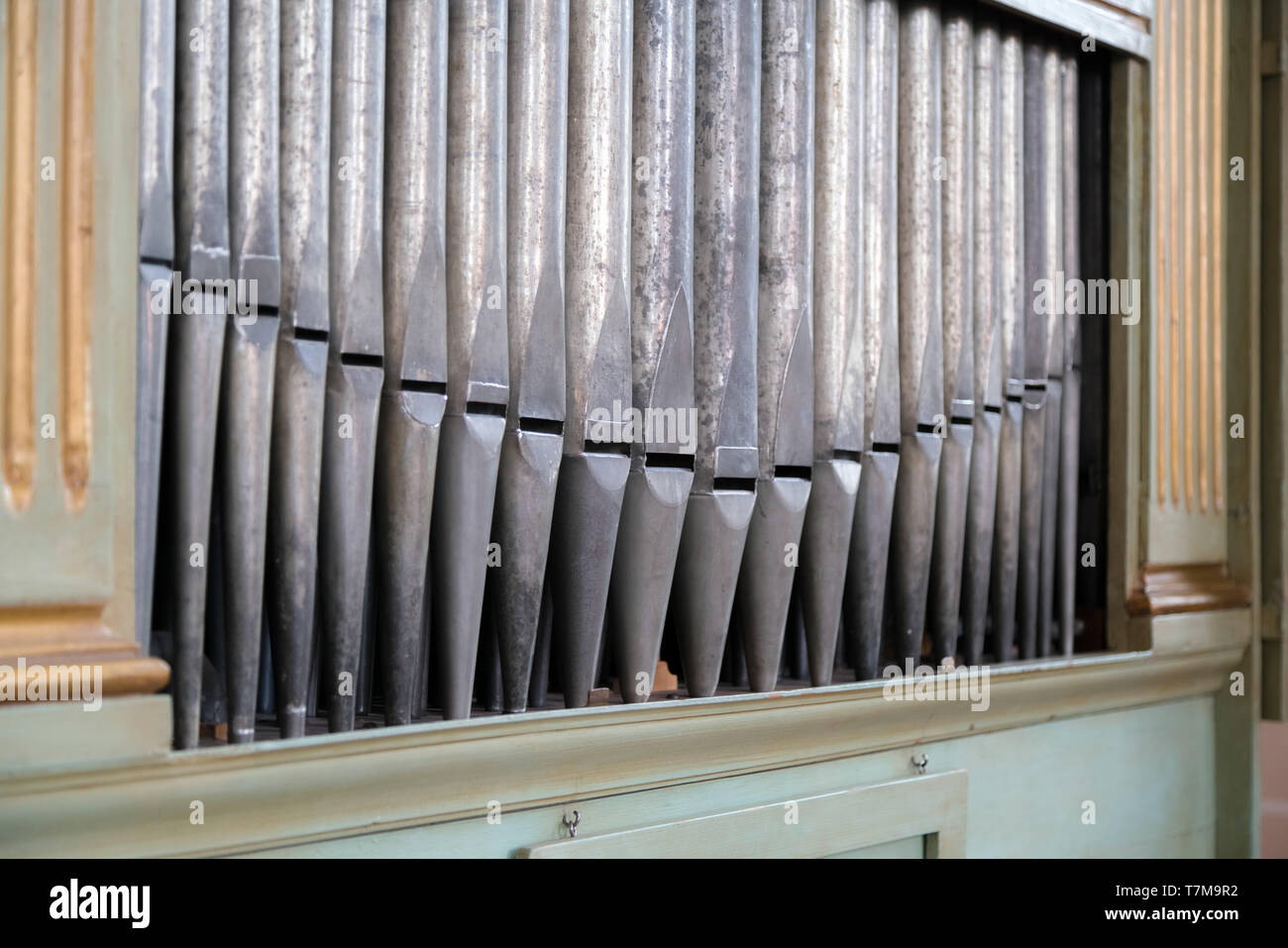 Old, silver organ pipes in a church used for playing sacred music. Many air pipes, sound tubes in the cathedral - Stock Image