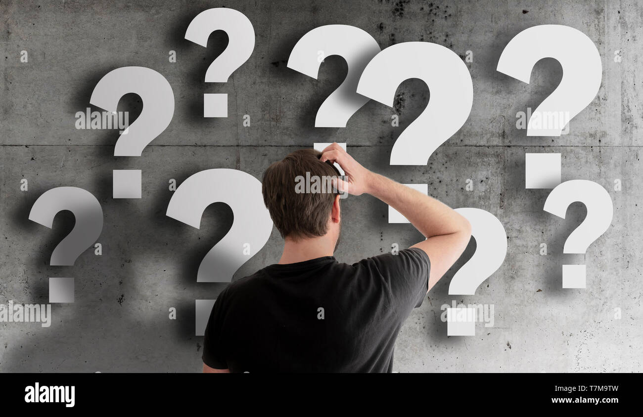 rear view of puzzled man scratching his head against concrete wall filled with question marks - Stock Image