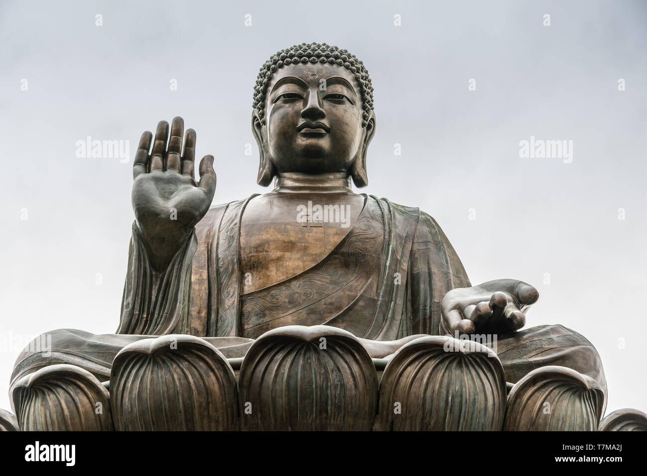 Hong Kong, China - March 7, 2019: Lantau Island. Frontal Facial closeup of Tian Tan Buddha statue from down under showing face, chest, and lotus leave - Stock Image
