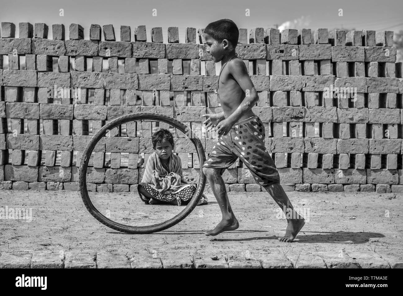 Kolkata : dated 04/02/2018, A village near brick kilin , people live in the mud houses, children play to run with waste tyre bear feet, small girls si Stock Photo