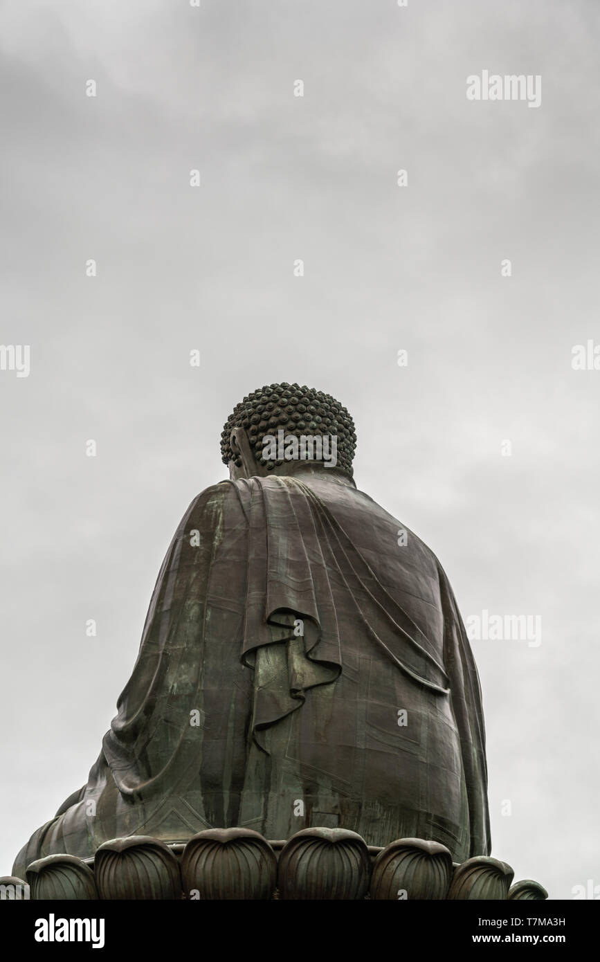 Hong Kong, China - March 7, 2019: Lantau Island. Tian Tan Buddha shows his back, statue from down under, back of body and lotus leaves under silver sk - Stock Image