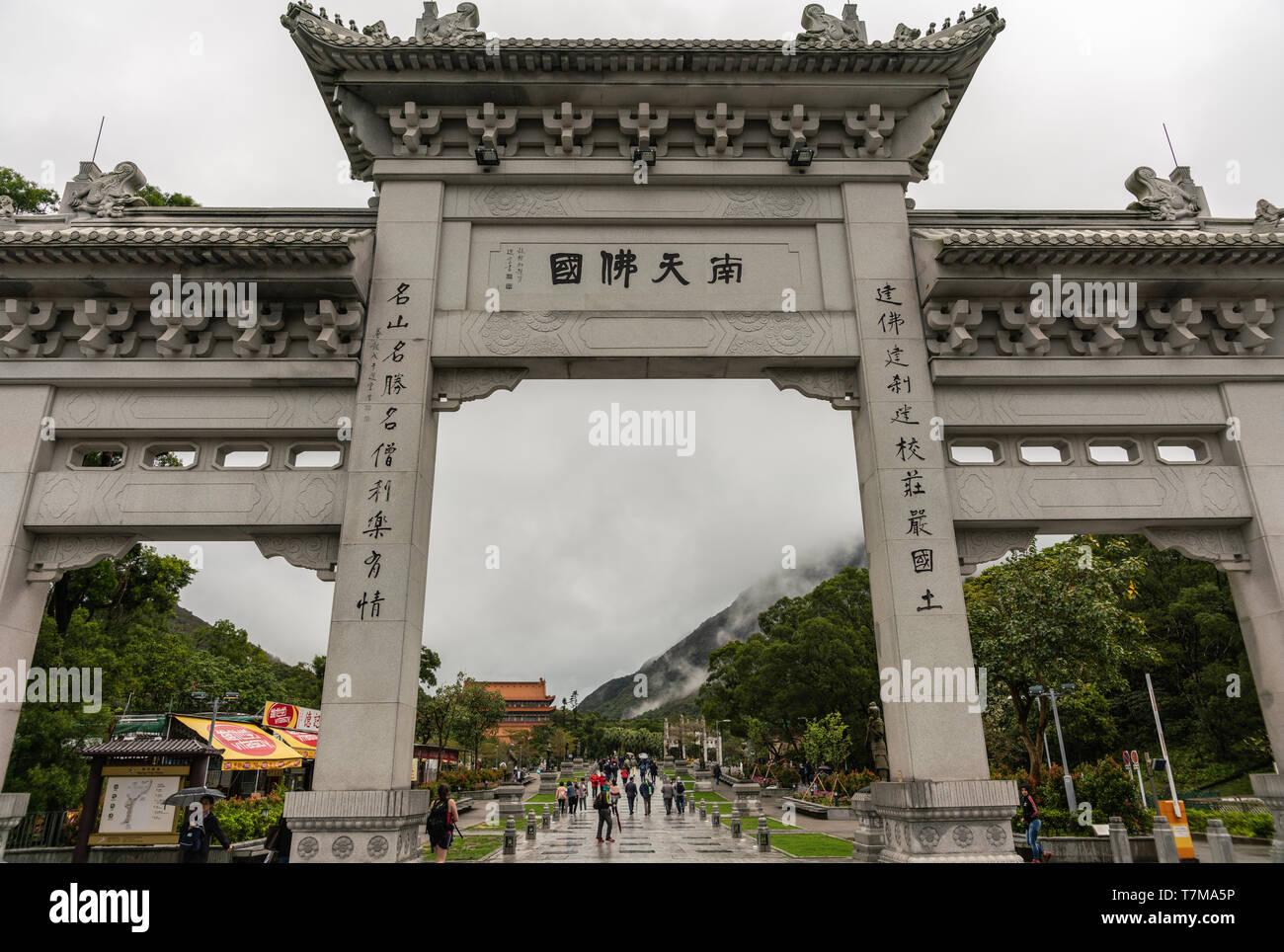 Hong Kong, China - March 7, 2019: Lantau Island, Po Lin Buddhis Monastery. Monumental gray entrance gate to the domain. Rainy conditions, green hills  - Stock Image