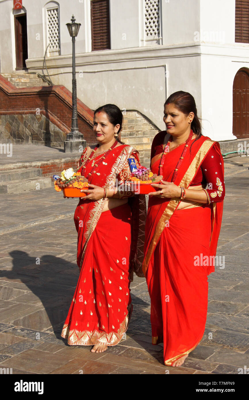 c7946082f Women in colorful red and gold saris hold religious offerings at  Pashupatinath Hindu temple, Kathmandu