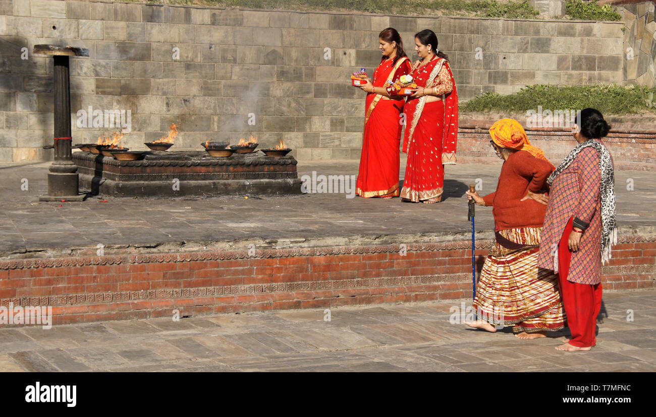 7e47b3a60 Women in colorful red and gold saris with religious offerings at place of  fire ritual,
