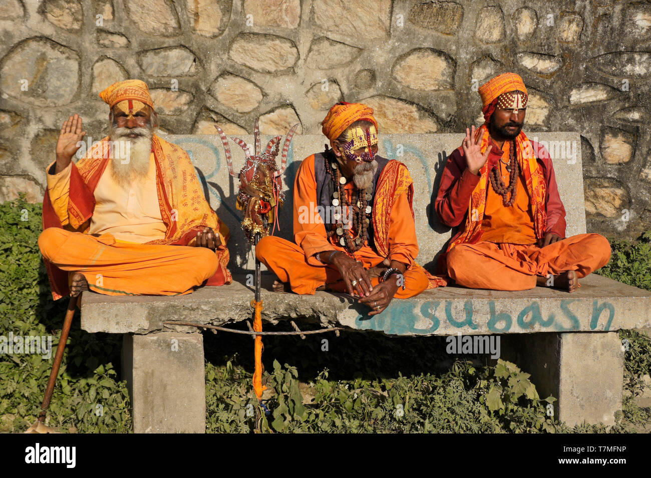 Three sadhus (holy men) with painted faces, clad in orange robes, sit on a bench at Pashupatinath Hindu temple, Kathmandu Valley, Nepal - Stock Image