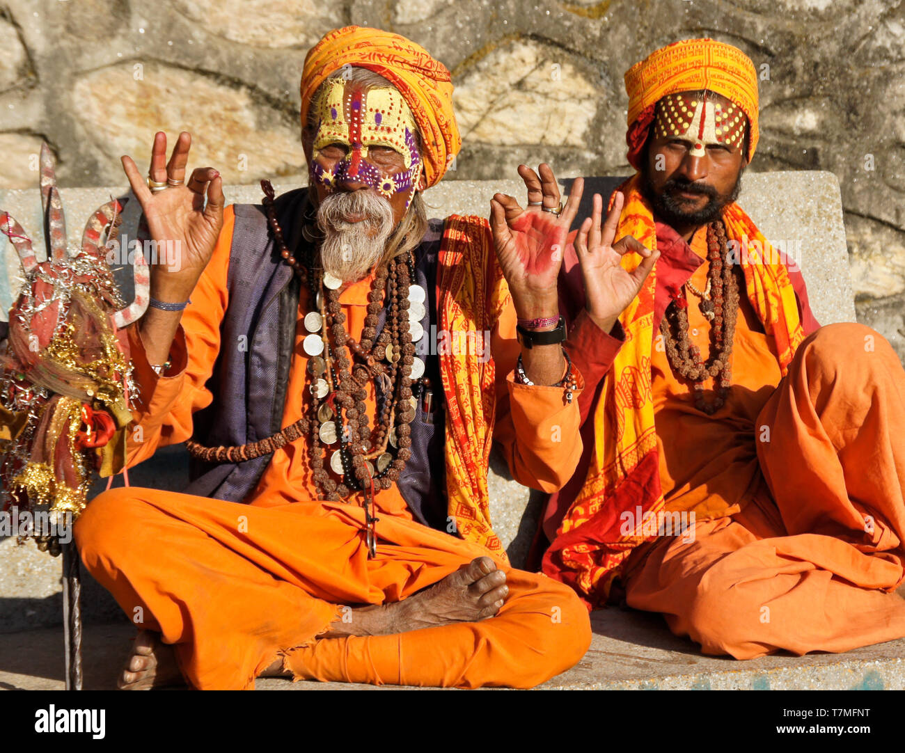 Two sadhus (holy men) with painted faces, clad in orange robes, sit on a bench at Pashupatinath Hindu temple, Kathmandu Valley, Nepal - Stock Image