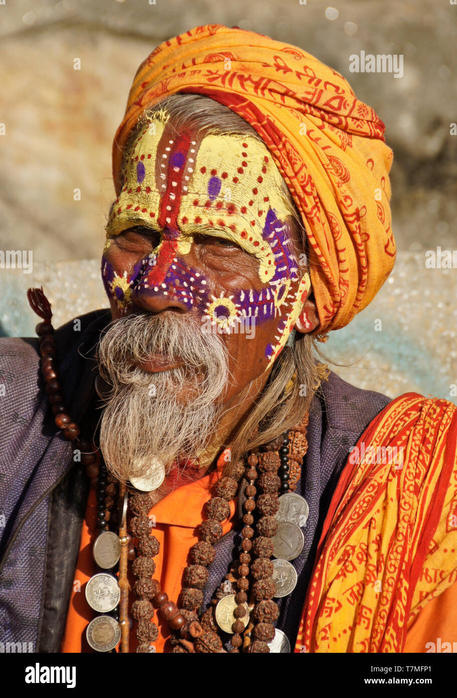 Portrait of a sadhu (holy man) with painted face, clad in orange robes, Pashupatinath Hindu temple, Kathmandu Valley, Nepal - Stock Image