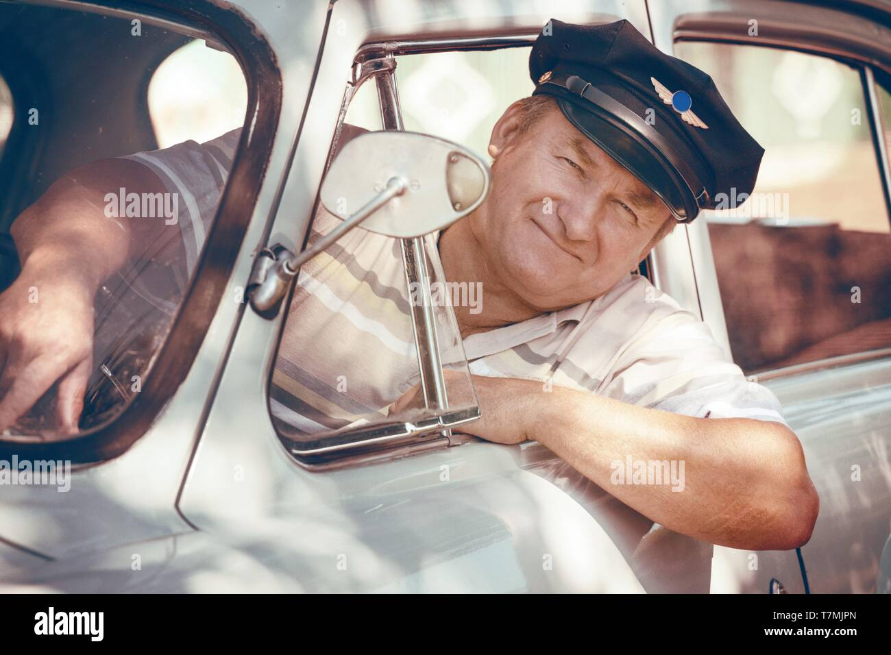 taxi driver looks out the window of a retro car Stock Photo