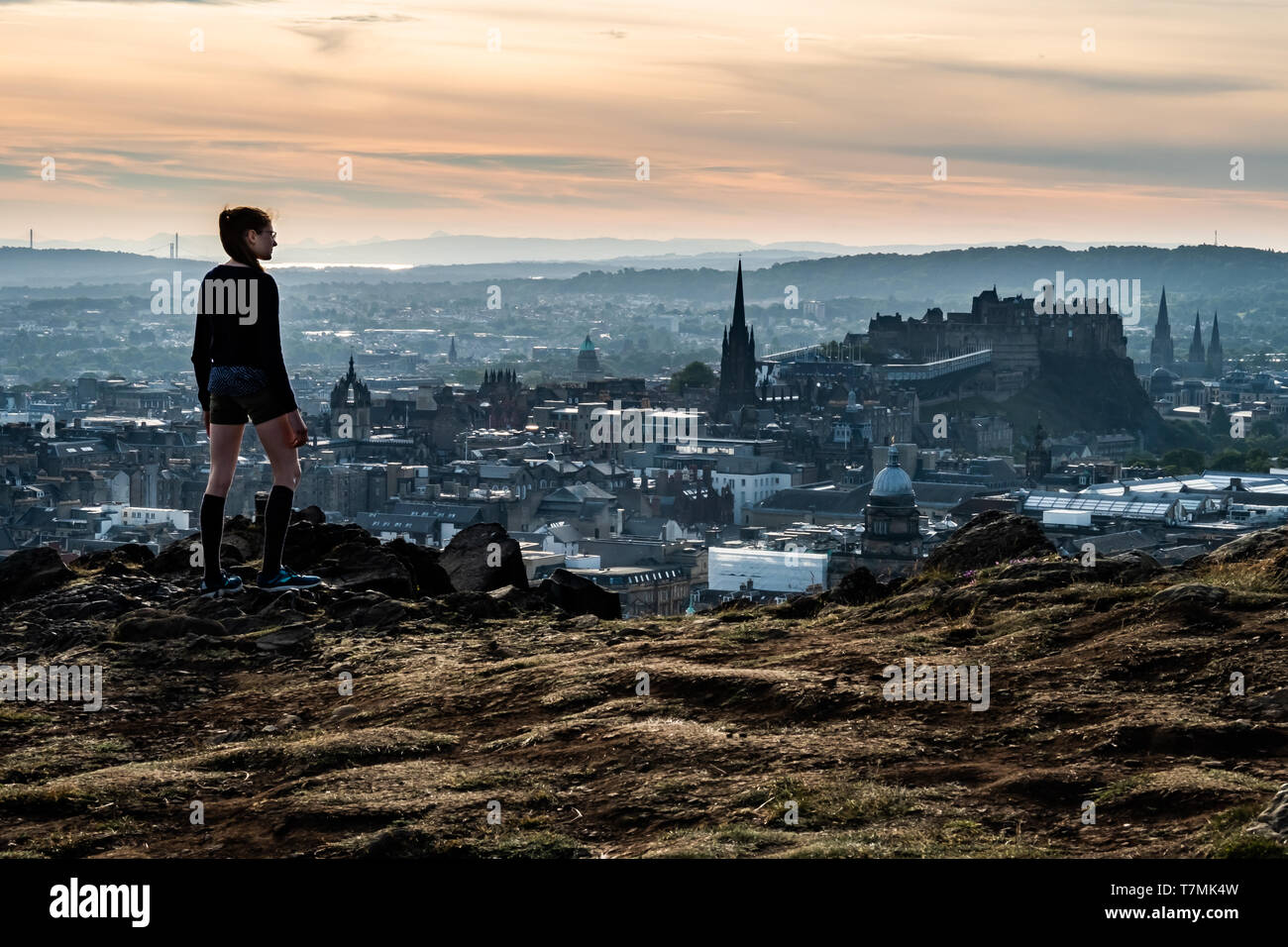 Overlooking Edinburgh from Salisbury Crags, a teen contemplates her future. - Stock Image