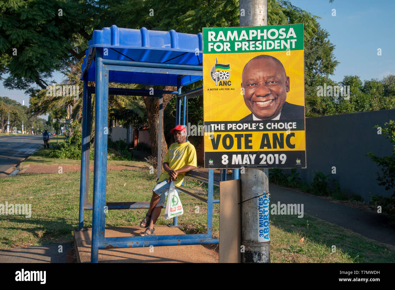 Johannesburg, South Africa, 7th May, 2019. A man waits at a bus stop as an ANC election poster is seen in Emmarentia on the eve of national elections, May 8. Credit: Eva-Lotta Jansson/Alamy - Stock Image