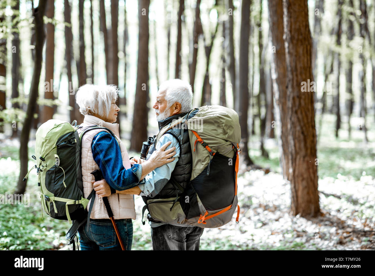 Lovely senior couple hugging in the forest while hiking with backpacks, back view - Stock Image