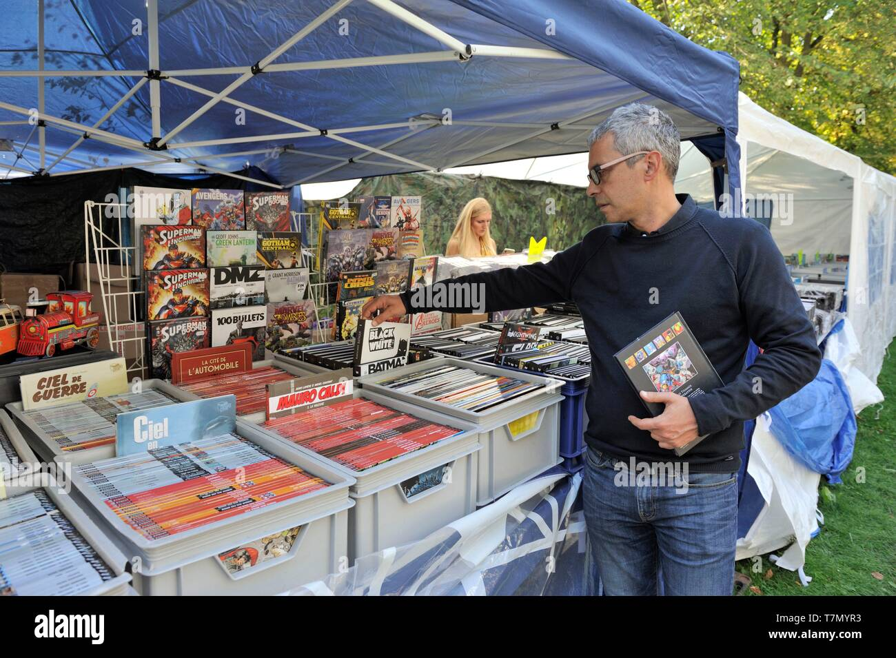 France, Nord, Lille, 2017 clearance sale, second-hand dealers along the esplanade, potential buyer leaving a book of a plastic crate - Stock Image