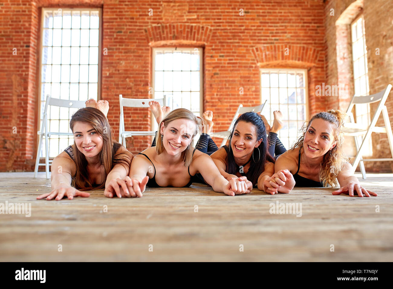 Group portrait of young sporty excited beautiful girls with exercise mats standing beside white wall laughing and talking together. Stock Photo