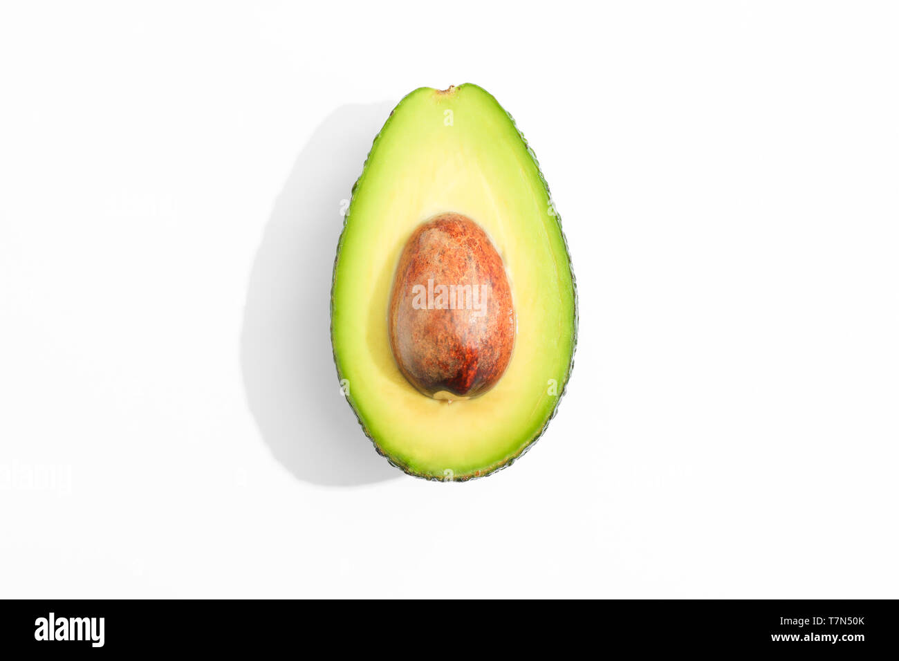 Rip cut avocado on white background, space for text - Stock Image