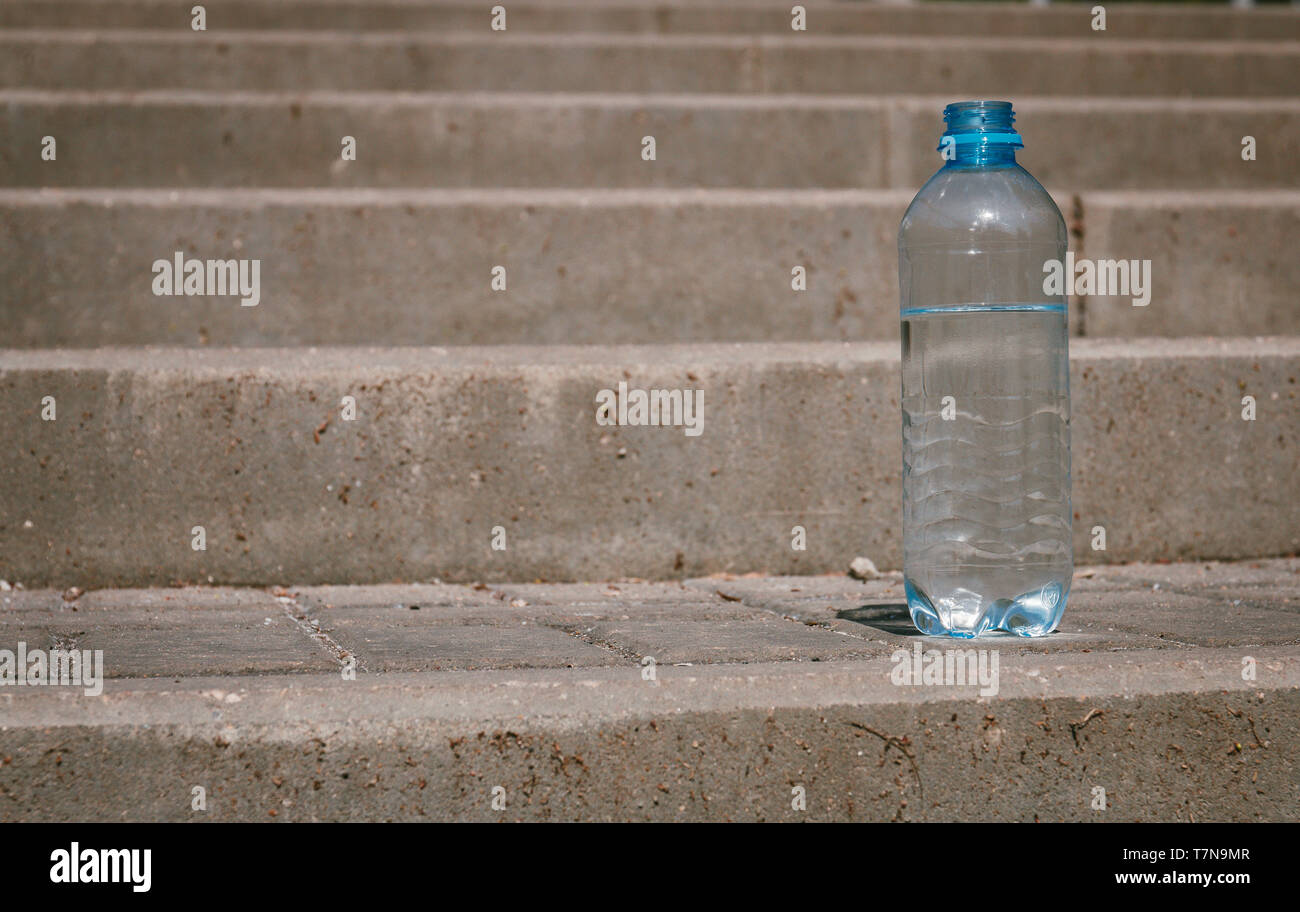 plastic bottle of clean drinking water on the road, source of life. - Stock Image